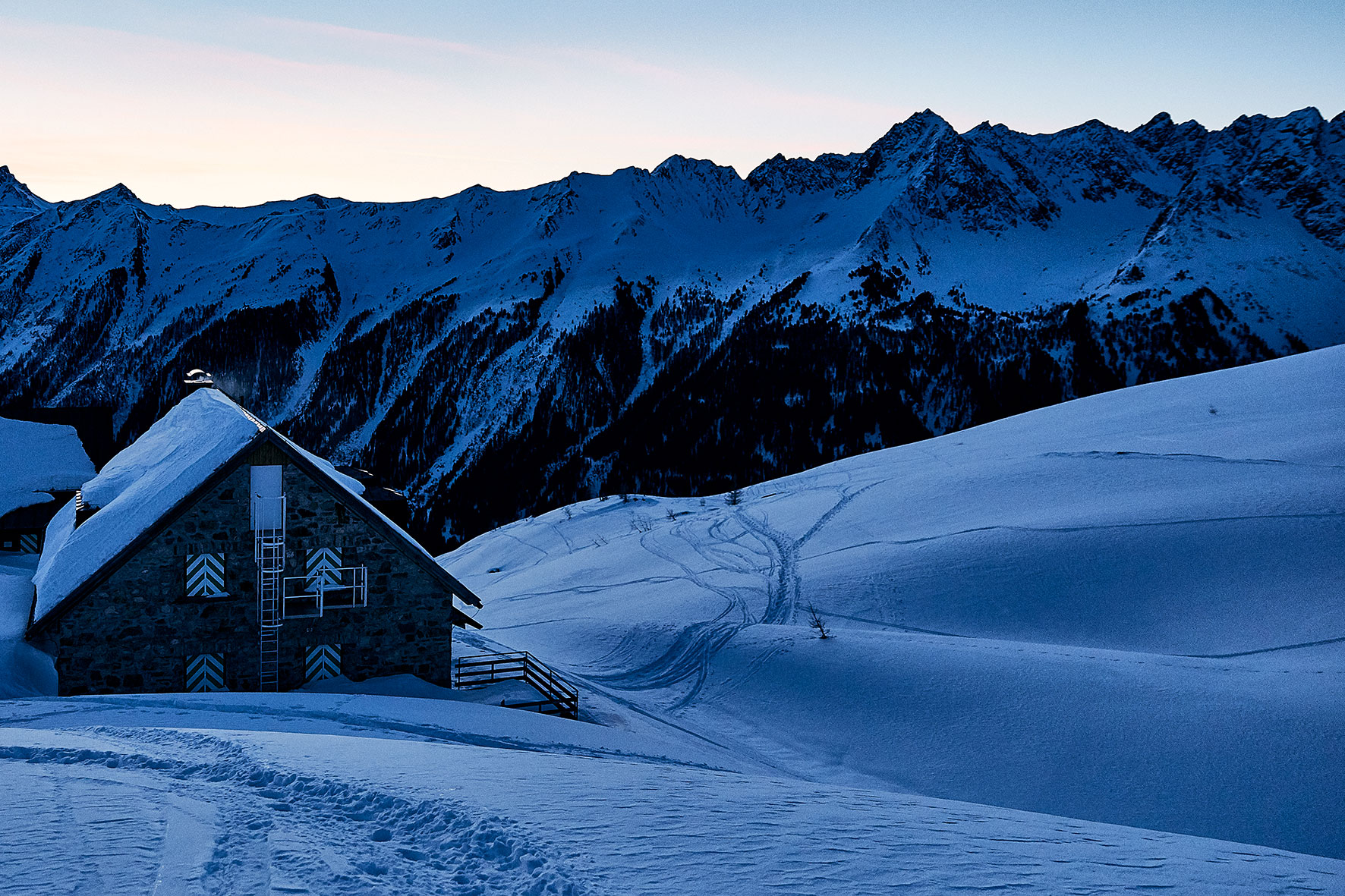 Photo of a winter night shelter ontop of the mountain before sunrise, the ski lines leading away from the hut and down the hill, with the mountain black in the background.e