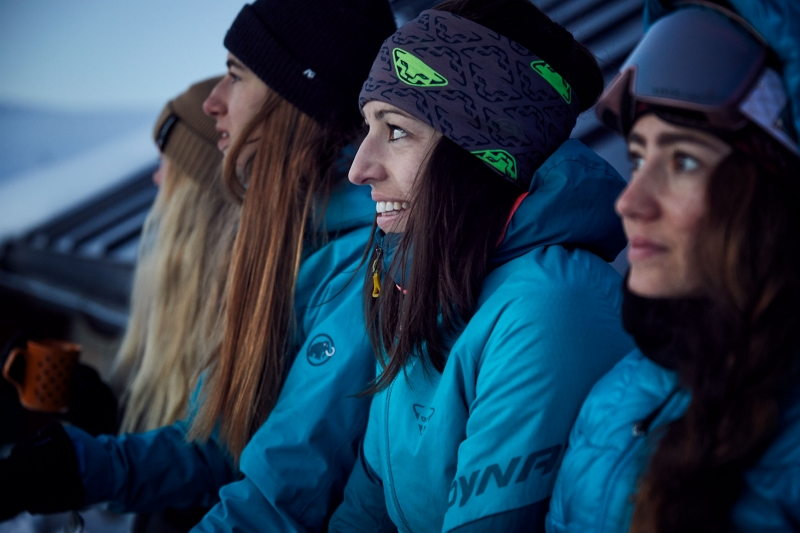 Four women in outdoor sport sitting against a night hut watching the sunrise over the mountain, dressed in ski clothes ready to go on a ski tour.