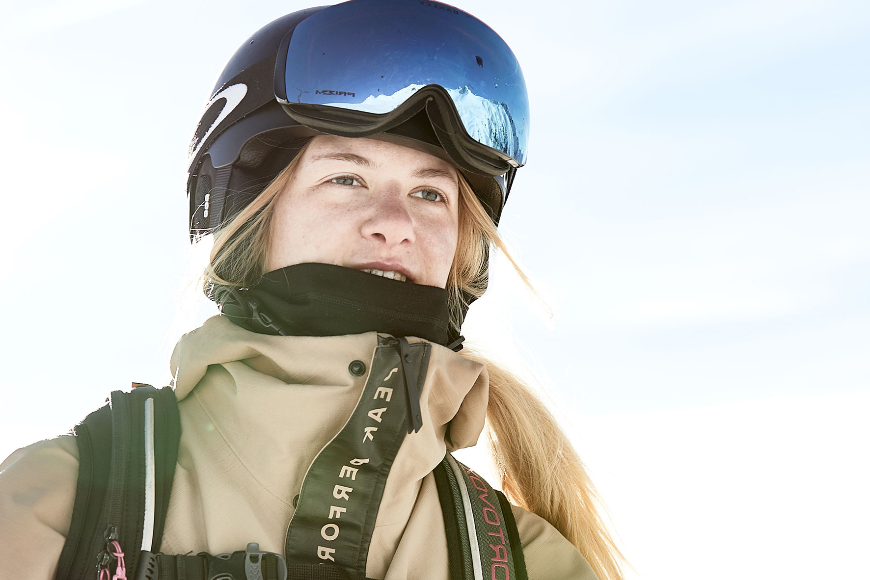 Portrait shot of a ski girl wearing a helmet and goggles while climbing the slopes on a ski tour.