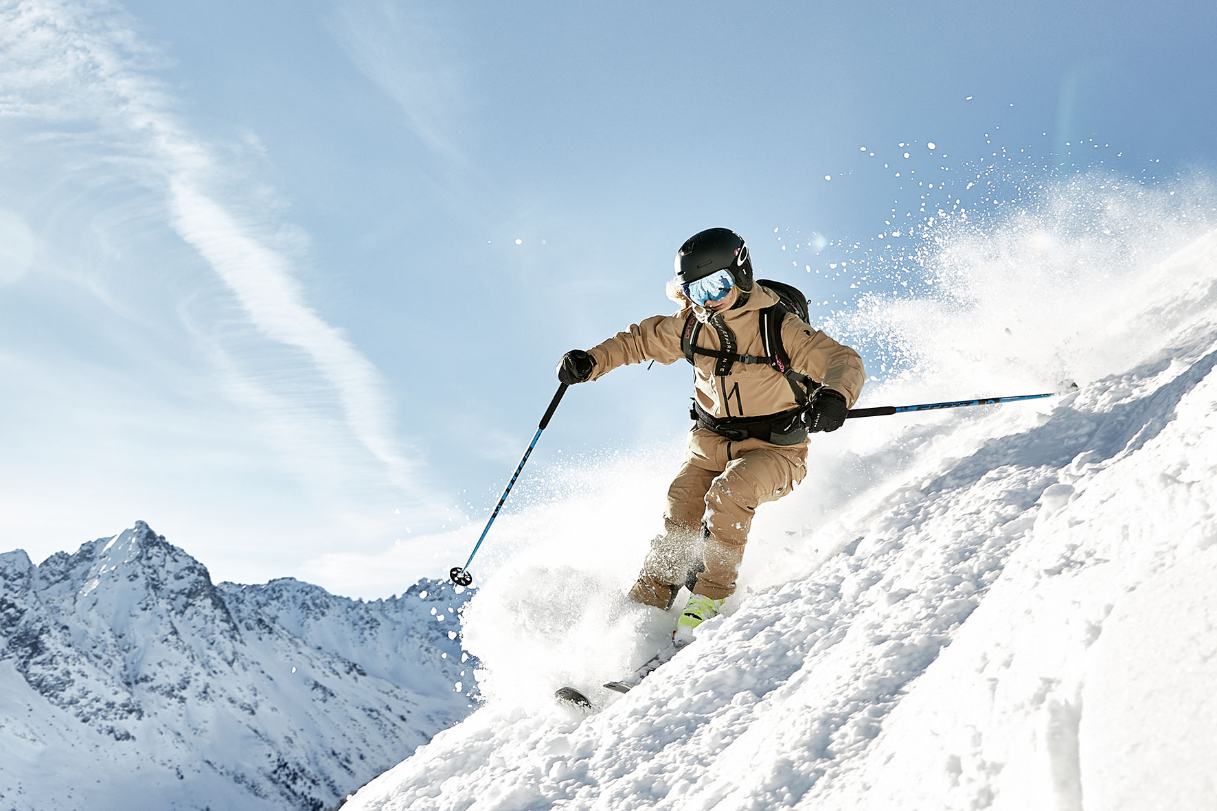 Woman skiing down a steep slope in the Alps near Innsbruck, with the snow spraying behind her and the mounains in the background
