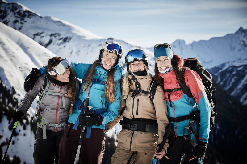 Four sporting women ontop of the mountain near Innsbruck posing for the camera in their snow gear.
