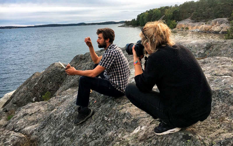 Jessica Zumpfe Photography perched on a rock overlooking the ocean in Sweden, shooting a sports model for a sustainable fashion brand, Hess Natur.