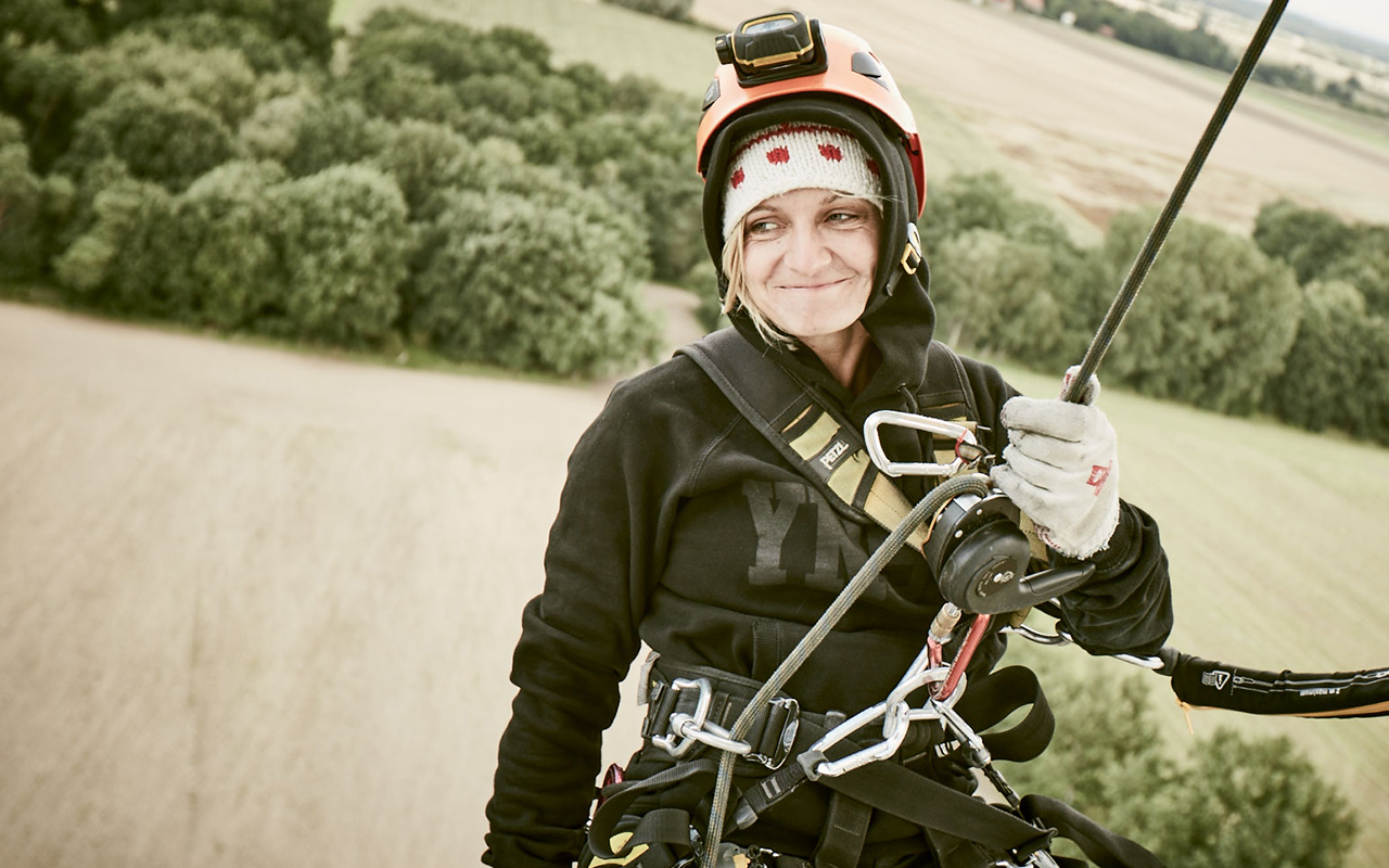 When you hire a photographer, you don't always expect them to abseil down a wind turbine. This is a photo of Jessica Zumpfe Photography at work - hanging in the ropes off a wind turbine while shooting
