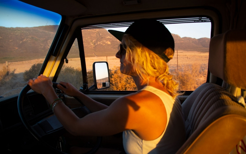 Cape Town photographer Jessica Zumpfe sitting behind the wheel of her 1985 vw camper van, driving through south africa's dry landscape while the sun sets.