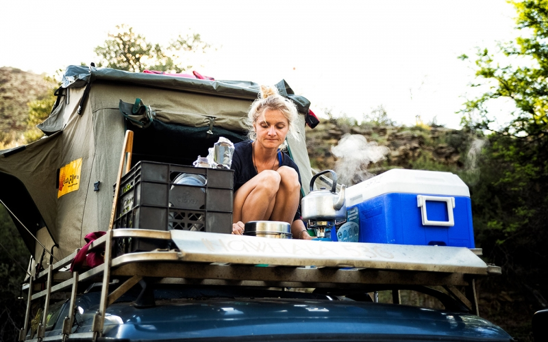 Professional photographer Jessica Zumpfe making tea in front of a rooftop tent ontop of a landrover discovery, somewhere in South Africa.
