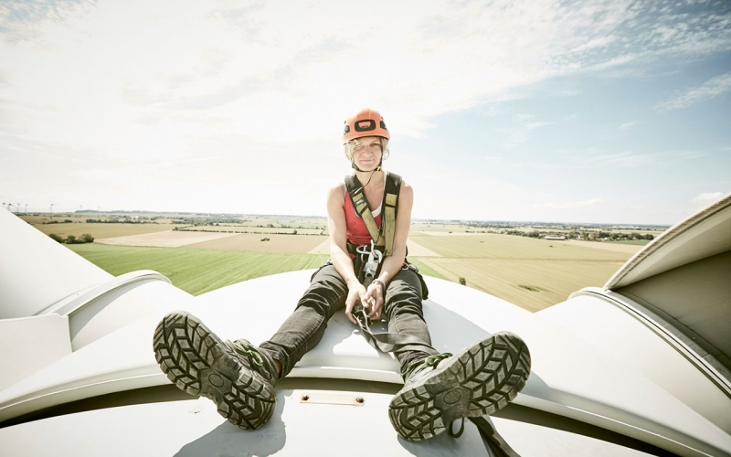 Cape Town photographer Jessica Zumpfe sitting on top of a wind turbine with a helmet and safety gear while on a shoot for a alternative energy client.