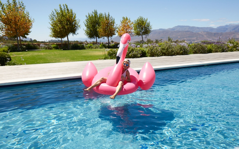 Jessica Zumpfe sitting on a pink flamingo in a pool near Cape Town, South Africa while on a shoot.