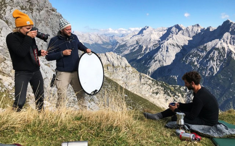 Professional photographer Jessica Zumpfe standing on top of the Karwendel mountain range while shooting a sports model for hess natur sustainable fashion brand. Next to her, her lighting assistant with a lighting reflector.