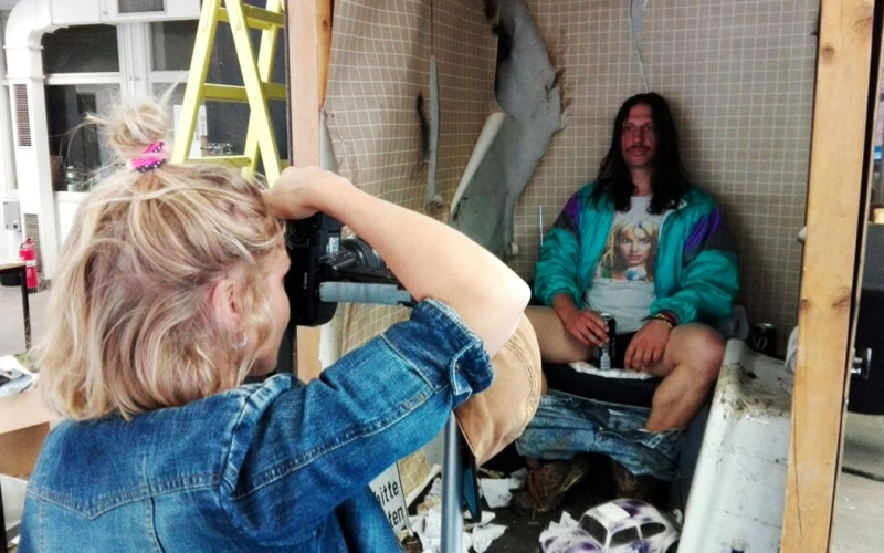 Over-the shoulder shot of Jessica Zumpfe Photography shooting a campaign for Goldeimer compost toilets, of the model sitting on the toilet, holding a beer between his legs.