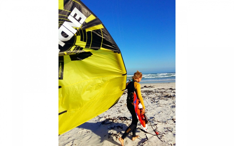Professional photographer Jessica Zumpfe carrying her kite onto her homespot beach in Muizenberg, Cape Town.