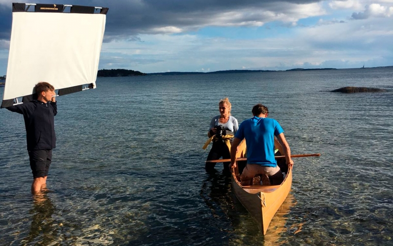 Professional Photographer Jessica Zumpfe standing in the sea in her wetsuit and shooting a sports model in a wooden canoe. Her assistant is standing next to her with a light reflector.