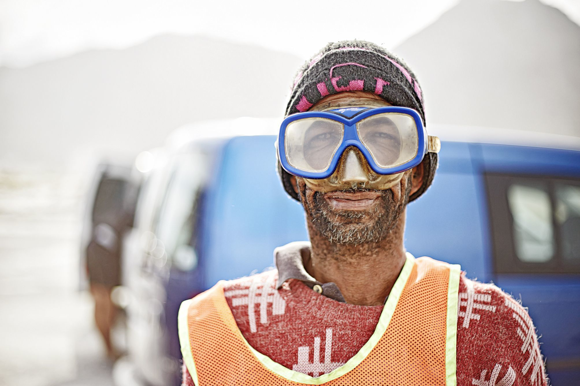 Portrait of David, the car guard at muizenberg kite sport sporting his underwater goggles, protecting him from the sand blasting.
