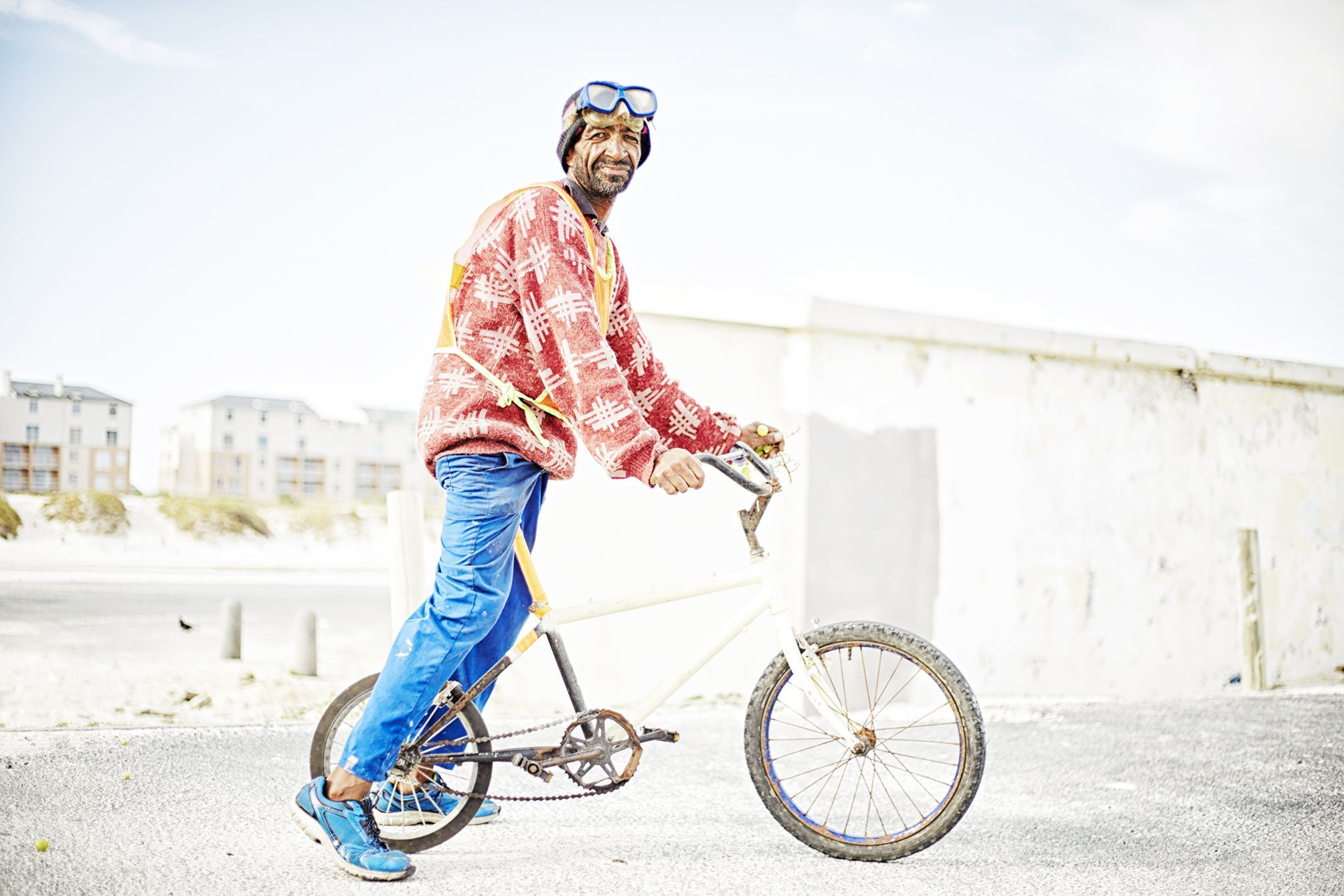 Portrait of Muizenberg's Car guard at the local kite spot sporting his bmx bike, goggles and some grapes.
