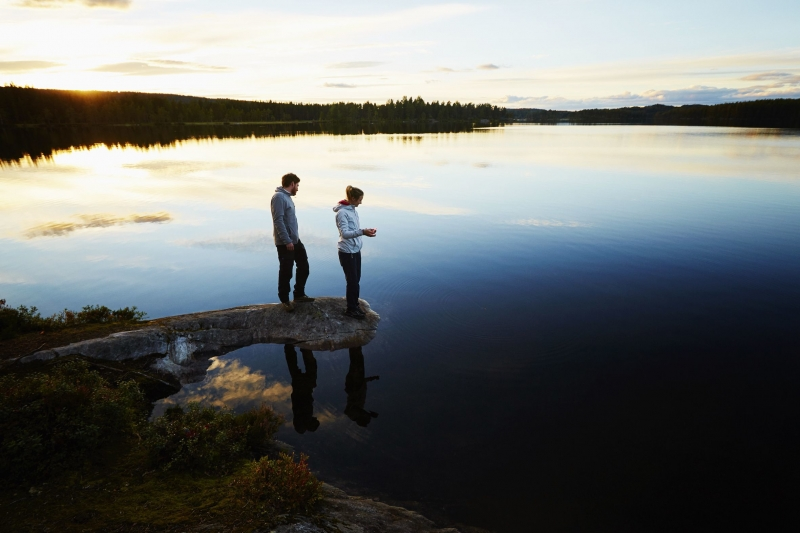 Couple fishing by a lake at sunset in Norway