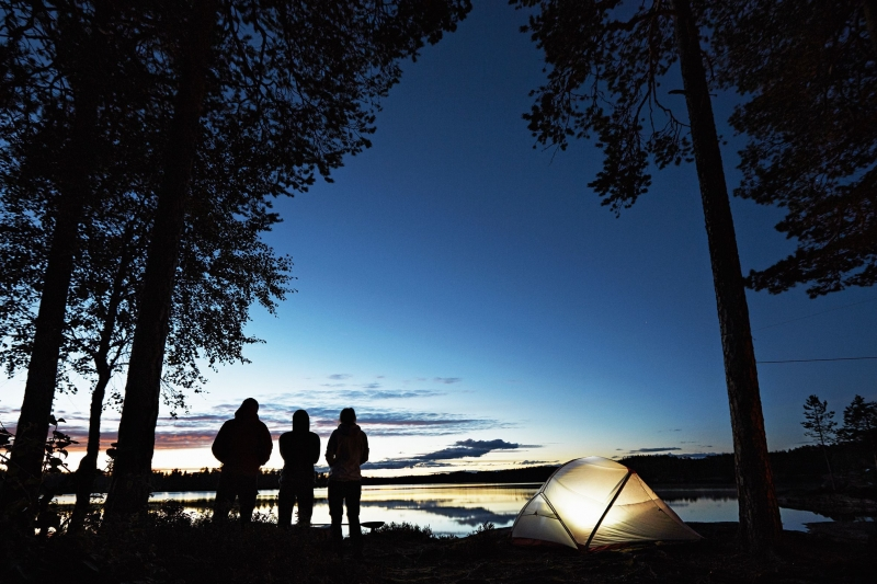 Silhouette of three people standing next to their lit tent under black trees by a lake near Oslo, Norway.