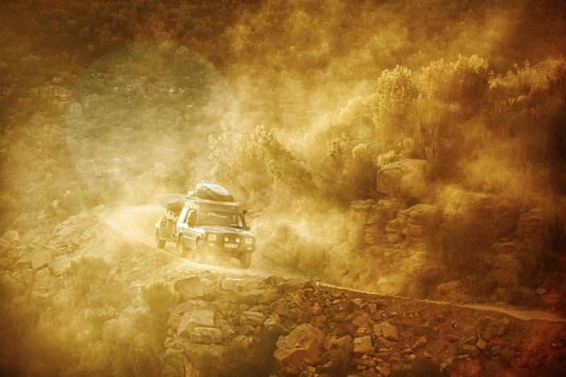Landrover Discovery rounding a corner in the mountains on a mountain pass, kicking up the dust in he sunset.