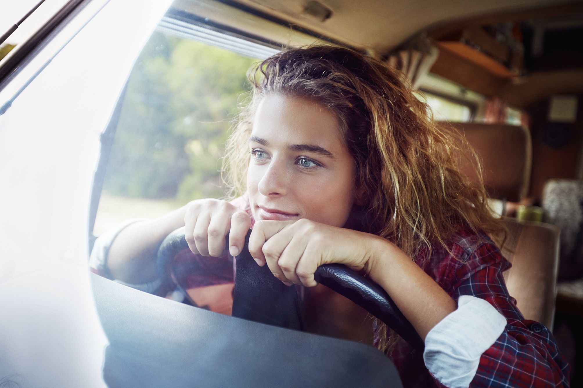 Young outdoor model sitting at the steering wheel of her vw camper van, gazing thoughtfully out of the window.