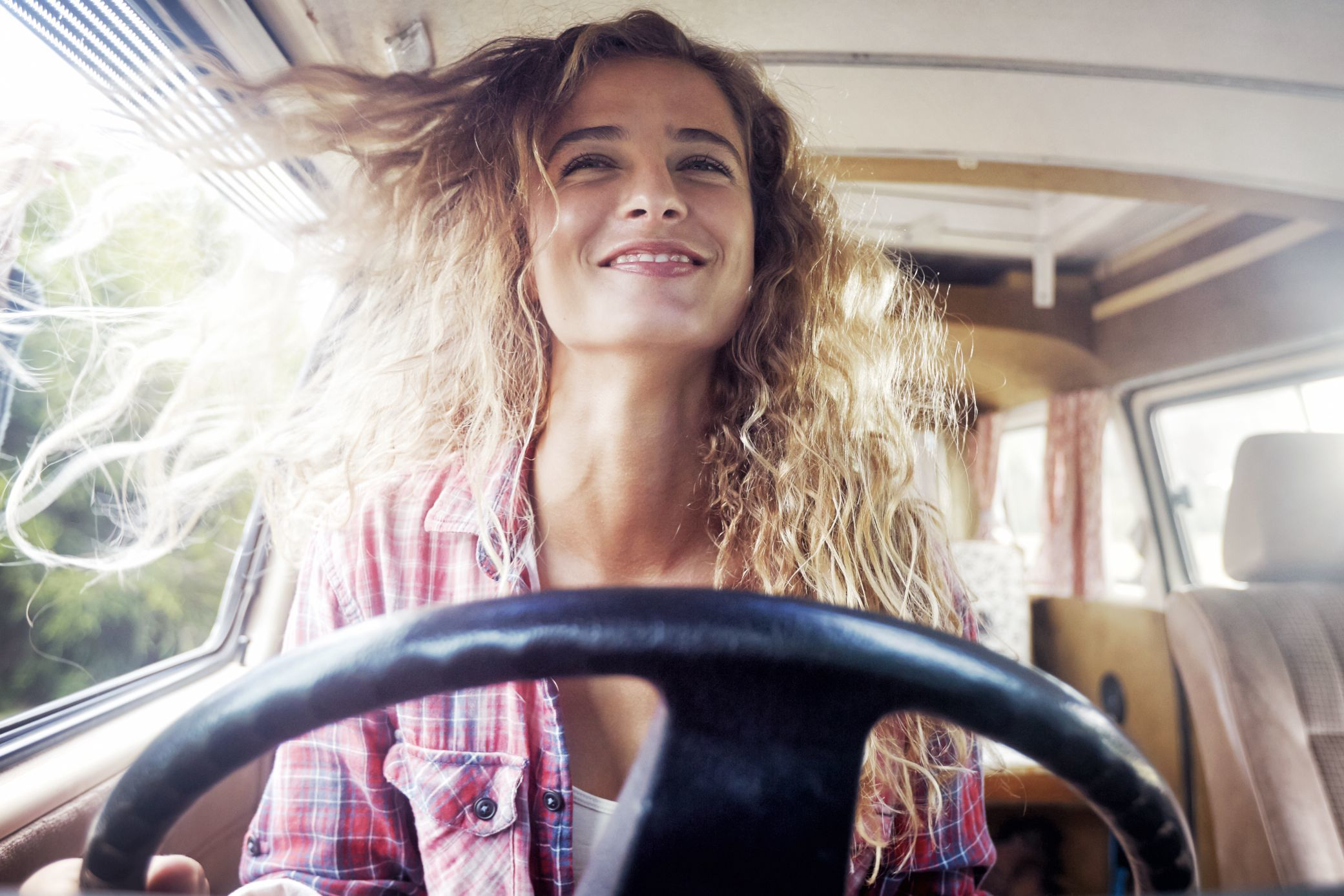 Portrait of a woman sitting at the wheel of her vw camper van smiling. Her hair is blowing in the wind. Shot as part of a self portrait story by Cape Town Photographer Jessica Zumpfe