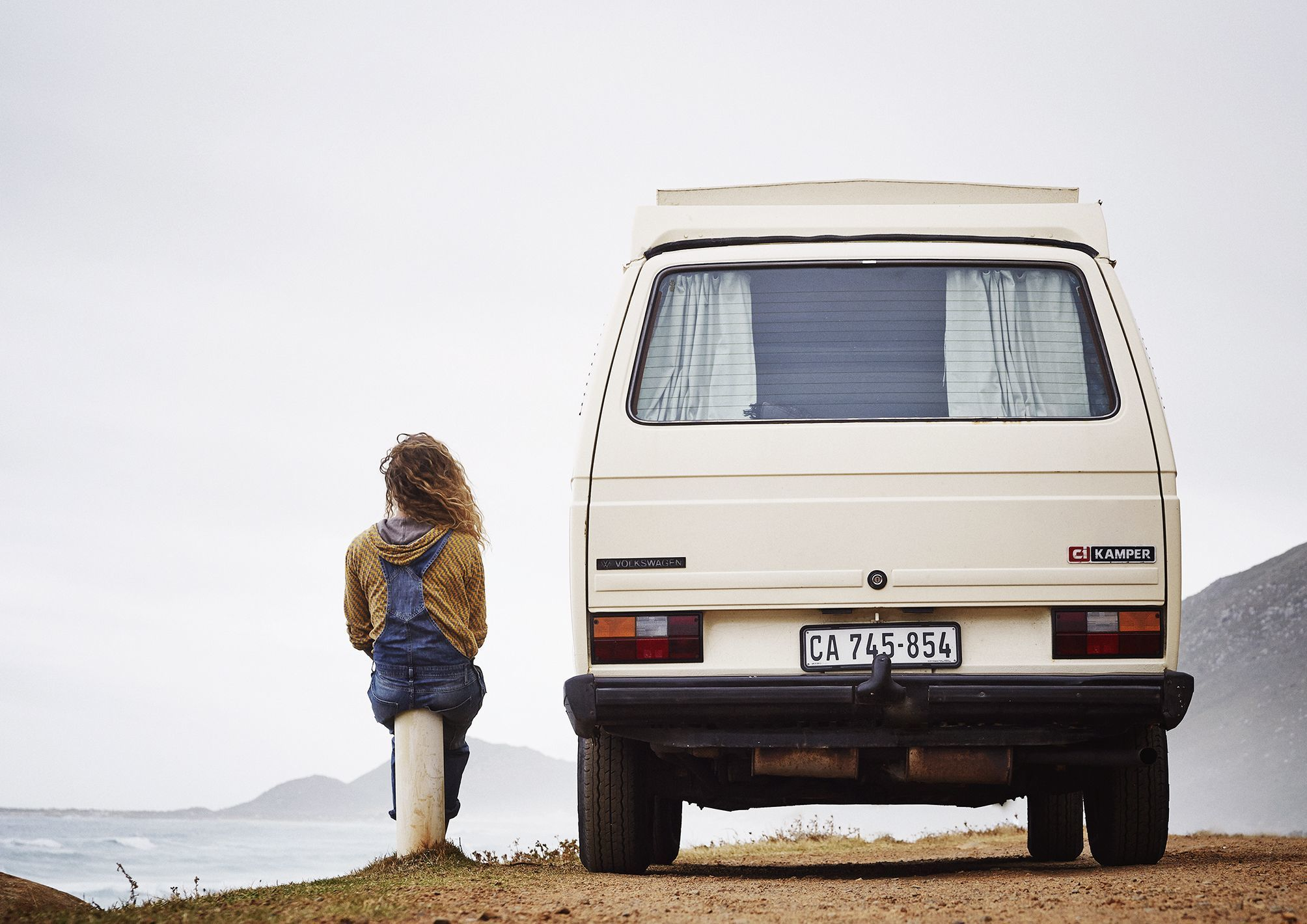 A girl sitting next to her van both enjoying the view over the ocean at misty cliffs in cape town.