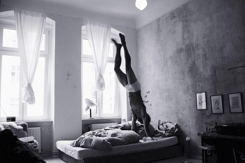 Portrait of an athlete doing handstands in his bed in Berlin