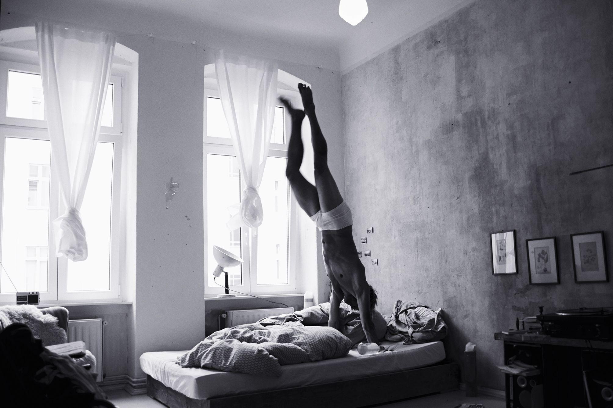 Portrait of an athlete doing handstands in his bed in Berlin