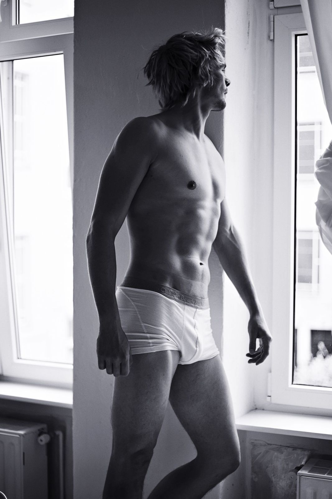 Athlete portrait of a young man standing next to a window in his schiesser underwear