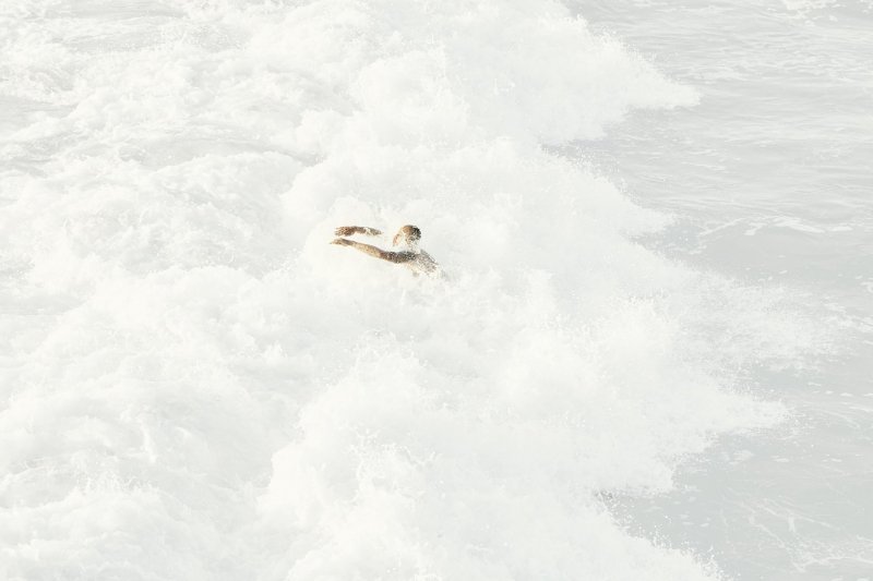 Man diving into the white wash of a wave in california.