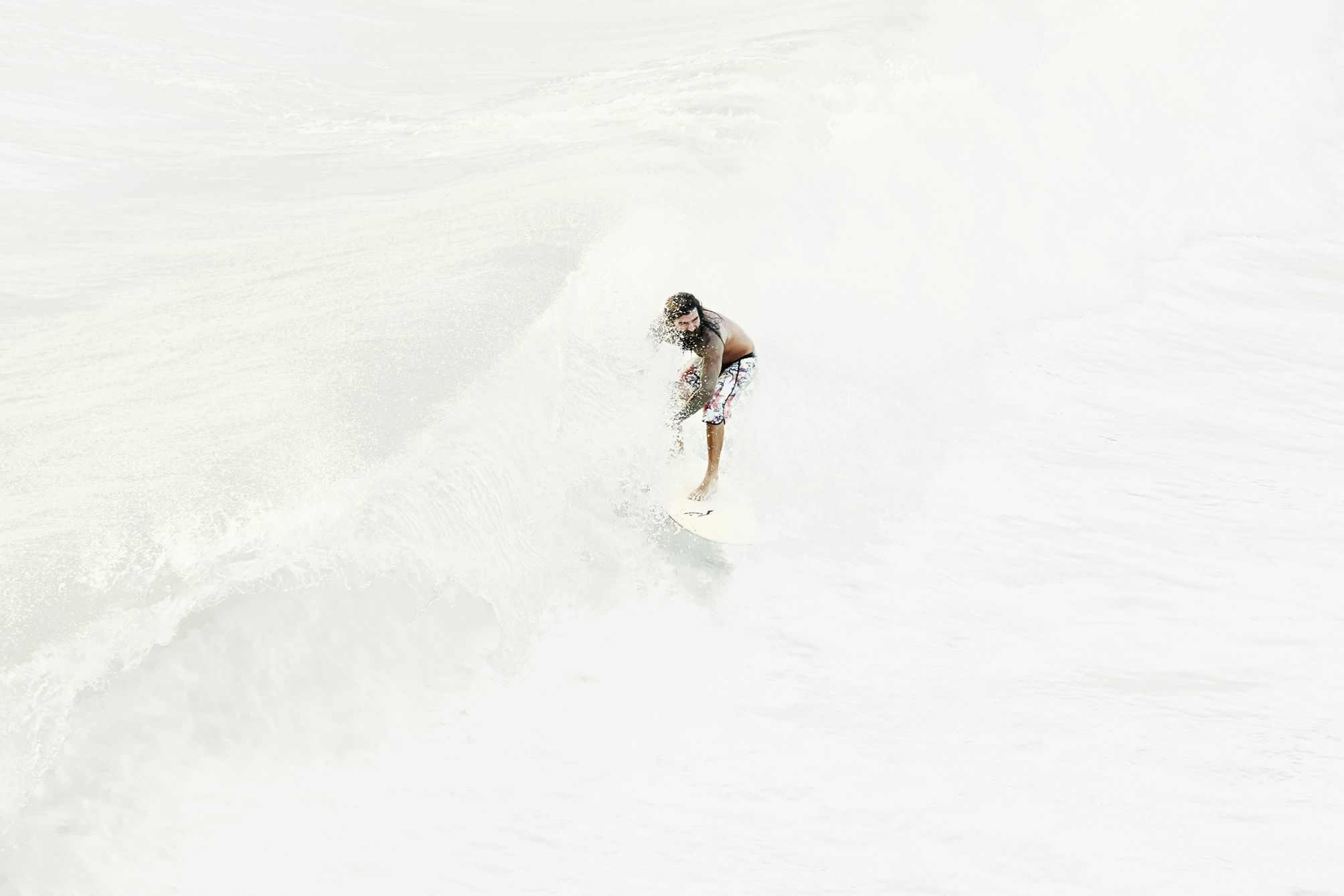 Surfer in a white sea surfing a wave.