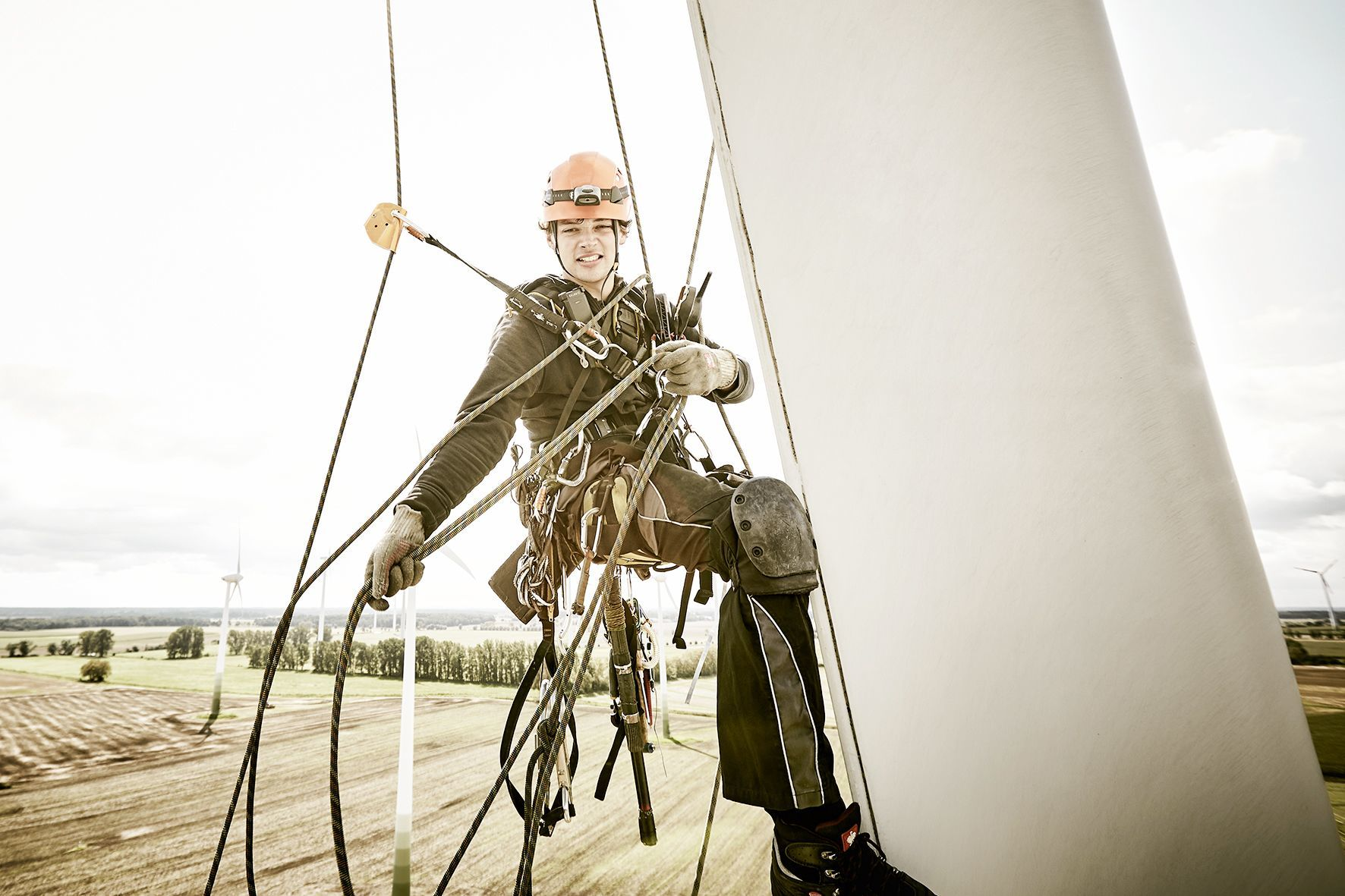 Close-up portrait of an industrial climber hanging in the ropes on a rotor blade, pulling the photographer who is hanging in the ropes beside him closer.