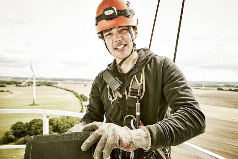 Portrait of industrial climber writting his protocol on top of a wind turbine on Fehmarn.
