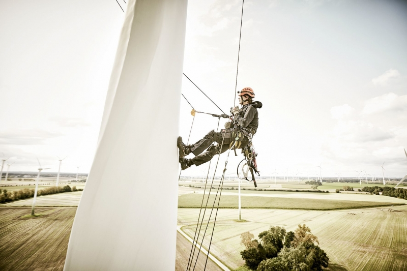 Rotor blade mechanic abseiling down a wind turbine with a view of the wind park on Fehmarn behind him.