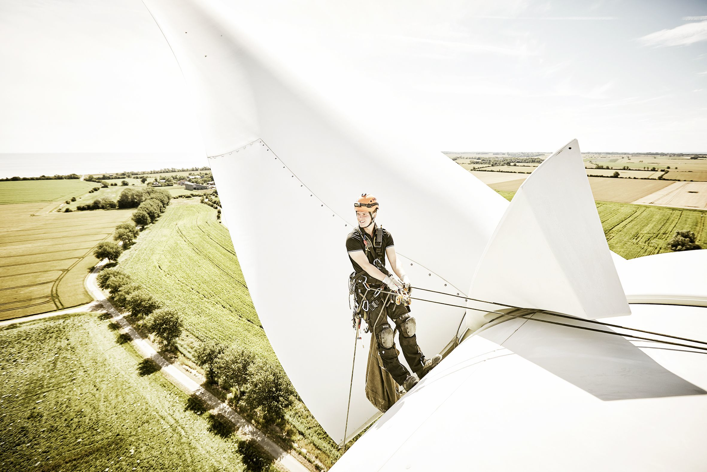 Industrial climber abseiling down a wind turbine with a magnificent view behind him.