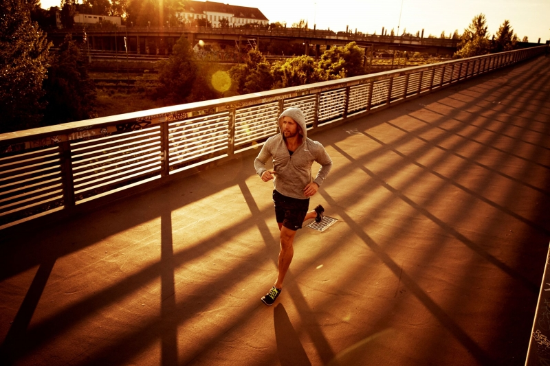 Urban sports trainer running over a bridge in the north of Berlin, the sun casting shadows from the reilings.