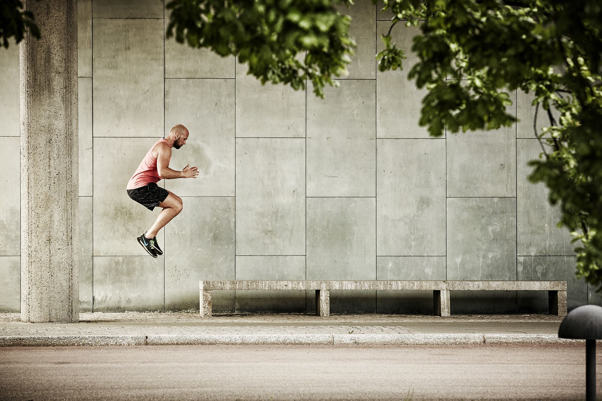 Fitness trainer jumping onto a bench