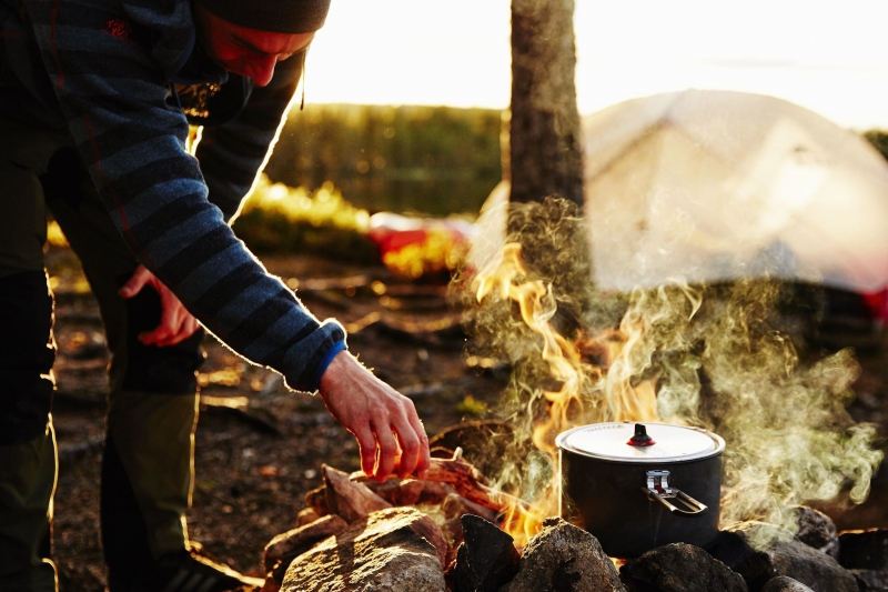 Young man stoking the fire at a campite of our expedition in norway, while cooking food over the fire.