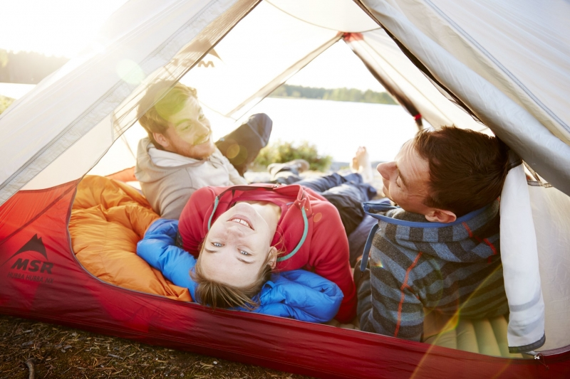 Group of friends lying in a tent laughing and looking up at the viewer. In the background is the lake district of Oslo, Norway