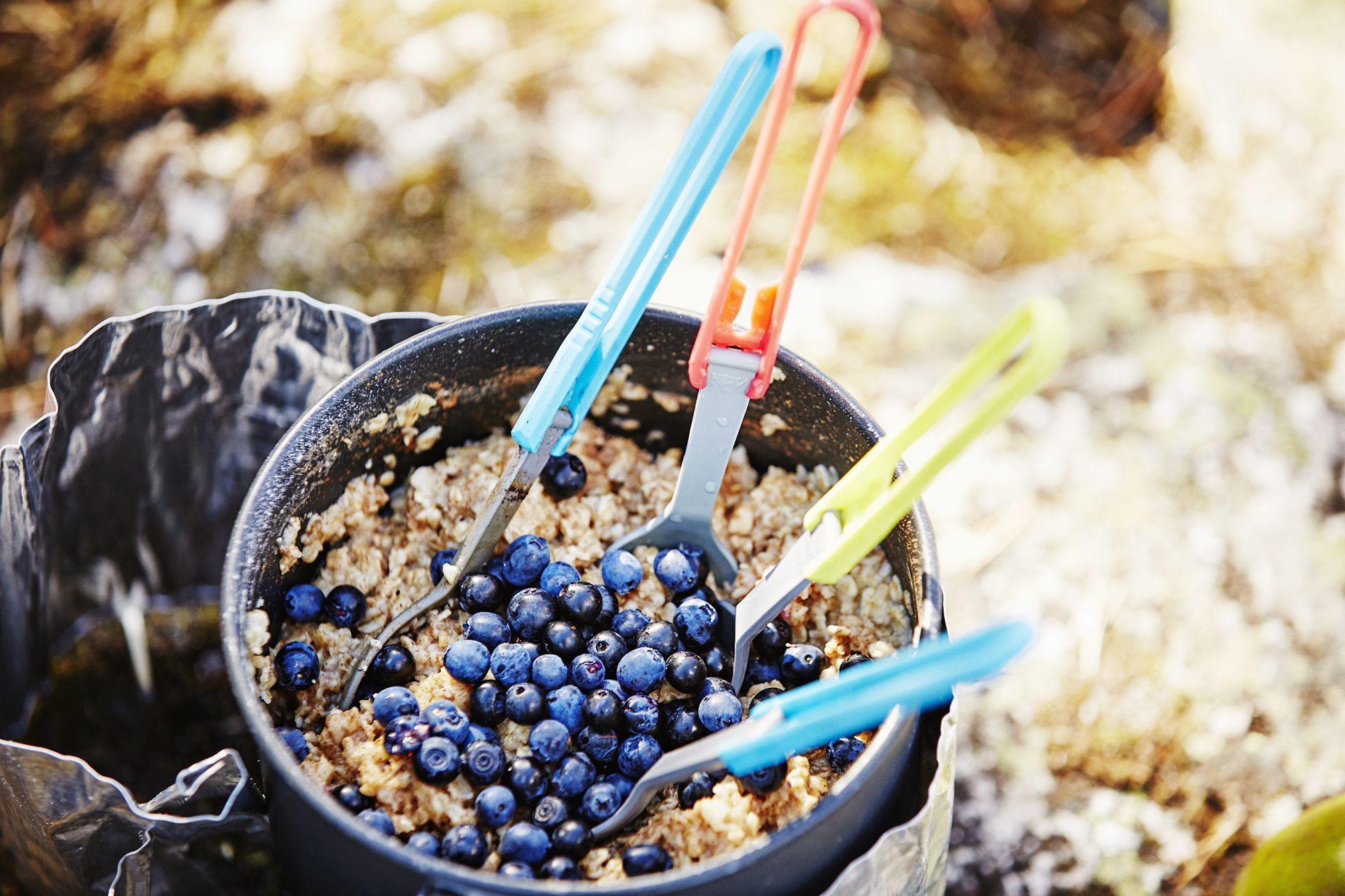 Image of breaktfast porridge with gathered blueberries and four colourful camping spoons on a cooker on a packraft expedition in Norway