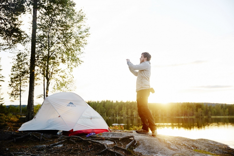 Young man taking a picture of his tent on his cellphone at sunrise near a lake in Olso, Norway.
