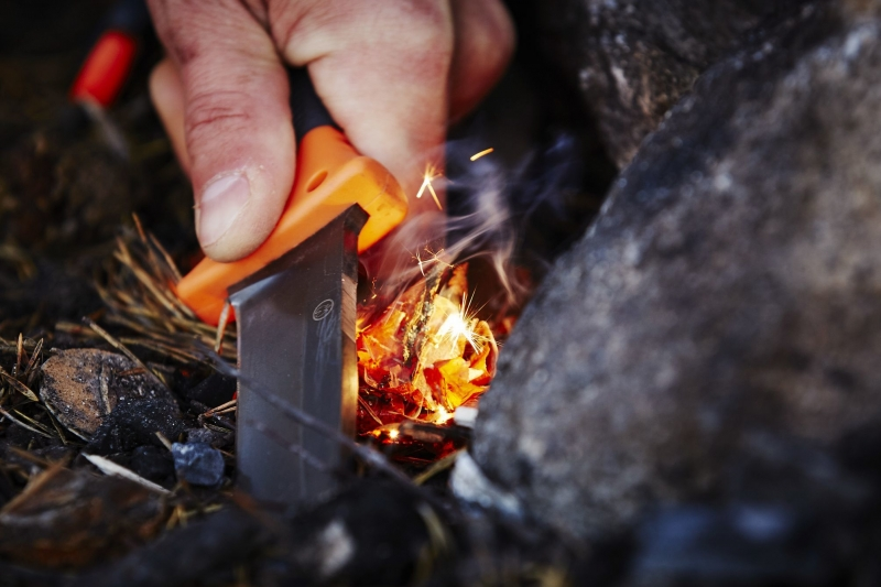 Picture of a hand lighting a fire with some birch bark and a spark knife in Oslo, Norway.