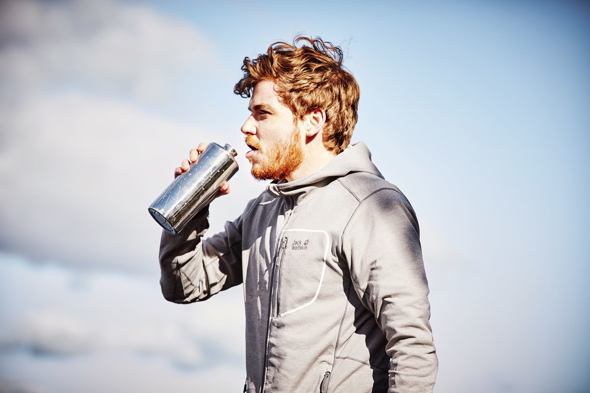 Young man juxtaposed infront of a semi cloudy sky in his jack wolfskin jacket drinking from a