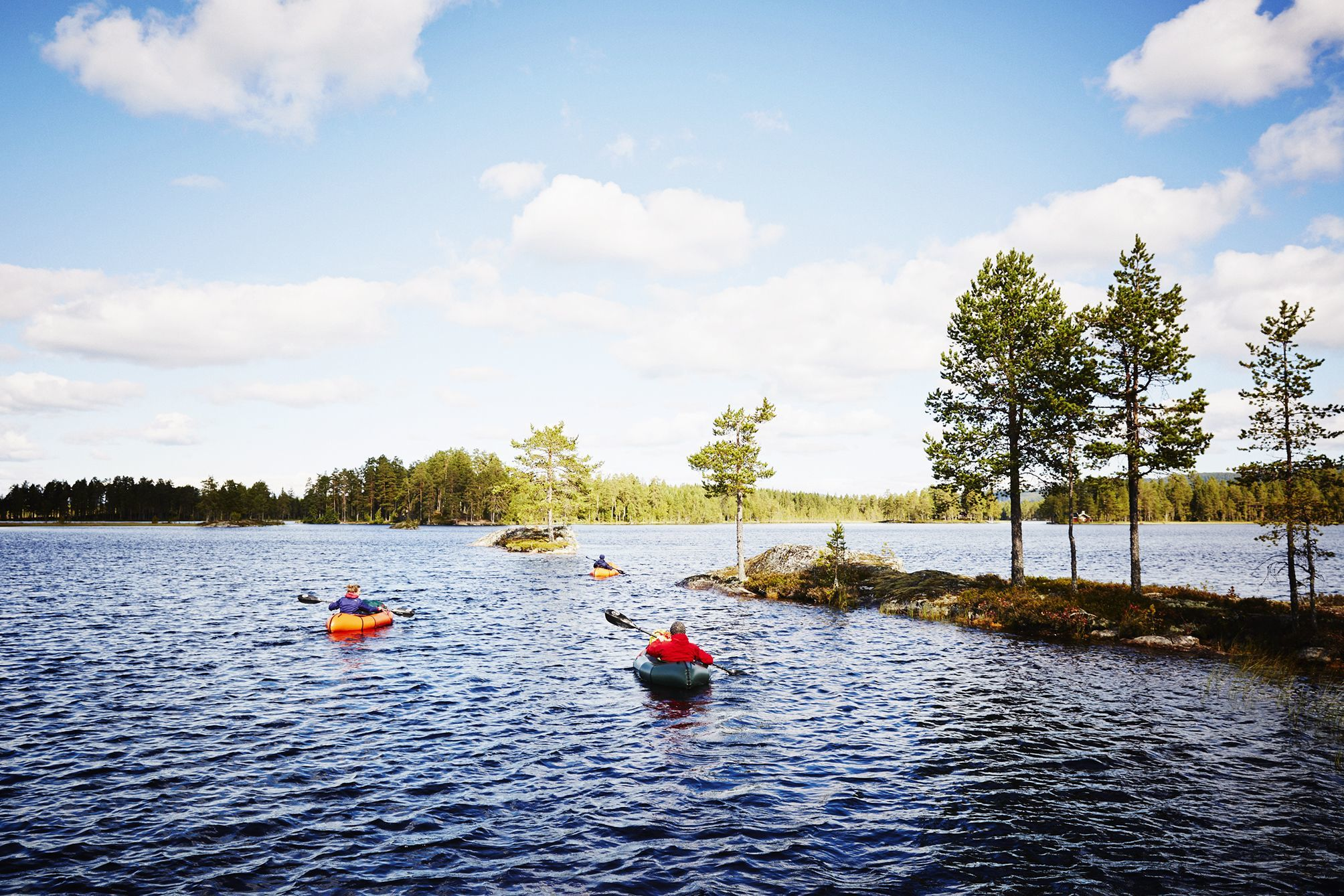 Group of packrafters navigating around islands in a lake district near Oslo, Norway