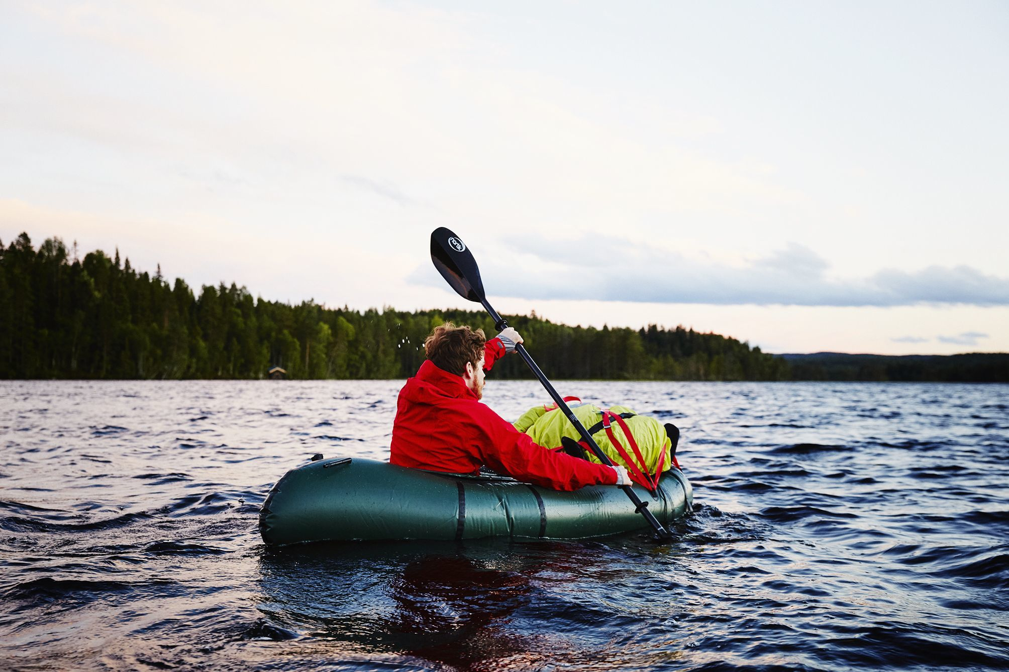 Young man paddling his packraft across a lake at dusk in the district near Oslo.