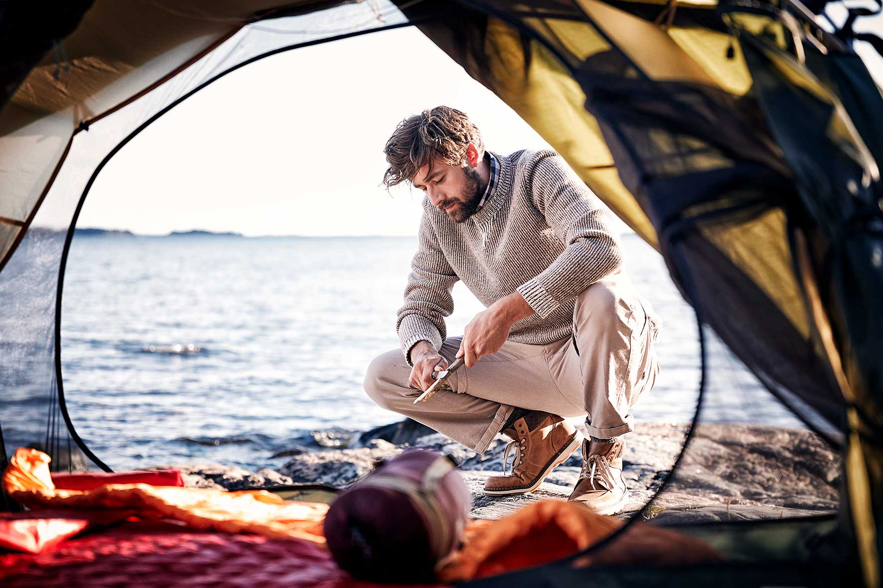 Nicklas crouching on a rock near the sea wearing fair fashion and whittling away at a stick, shot through the inside of his tent.