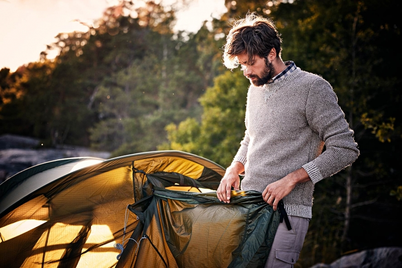 Young man rolling up his tent at dawn while wearing fair fashion clothes near Stockholm, Sweden.