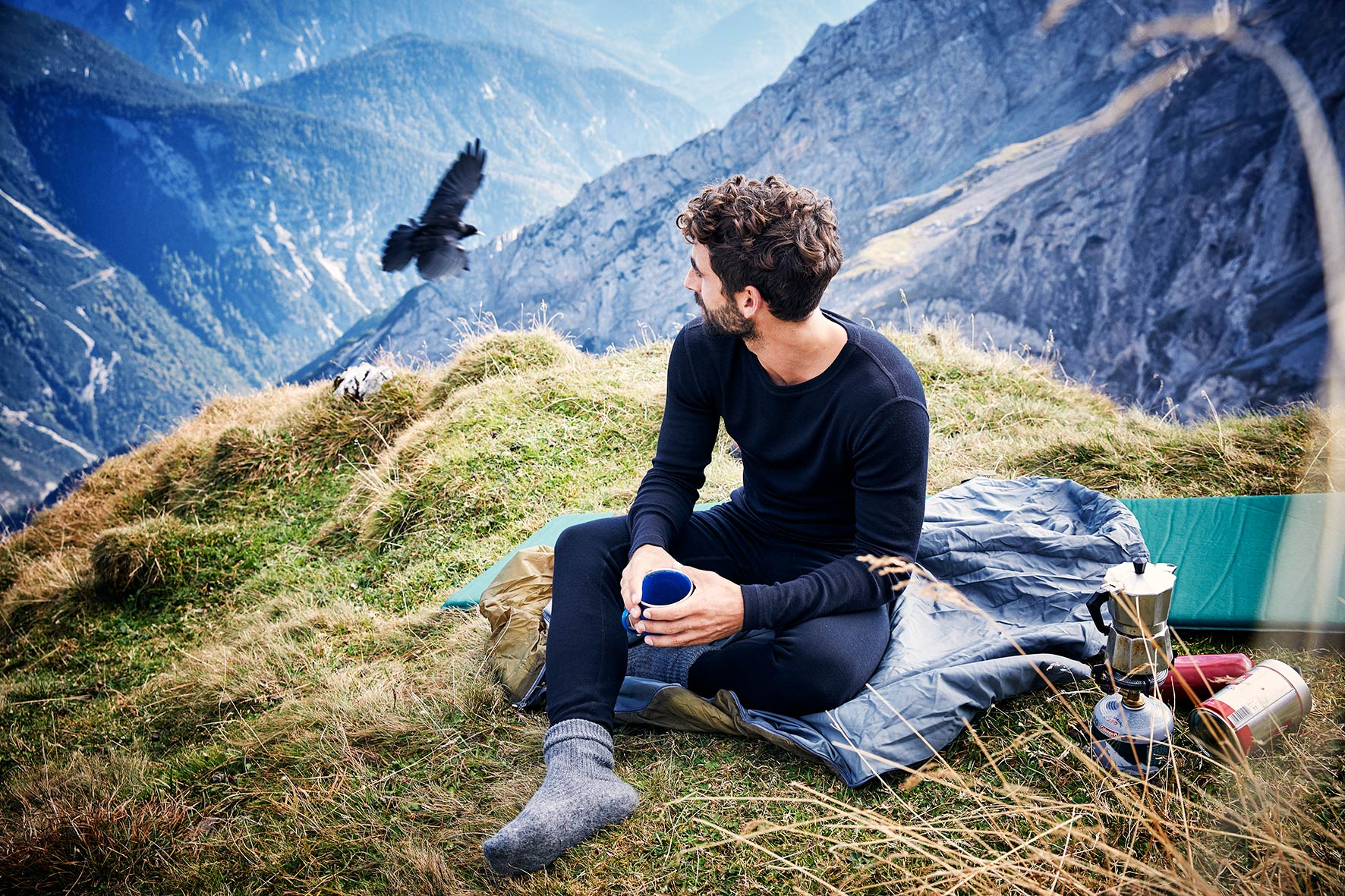 young man relaxing on a mountain while wearing sustainable fashion sports wear