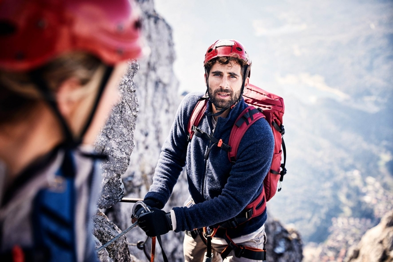 Young Man climbing a fixed rope route while wearing a helmet in the austrian alps