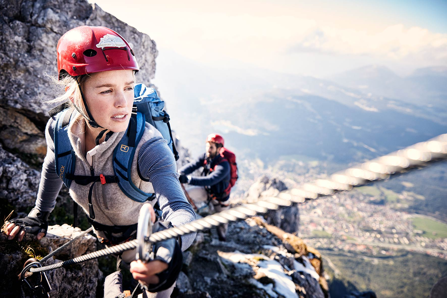 Sports photography models Hannah and Carlo climbing a via Ferrata at the Karwendel Mountain range, with Mittenwald in the background and far below them.