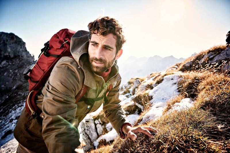 Young sports model carrying his ortovox backpack up the mountain in spring, with a few snow fields behind him.
