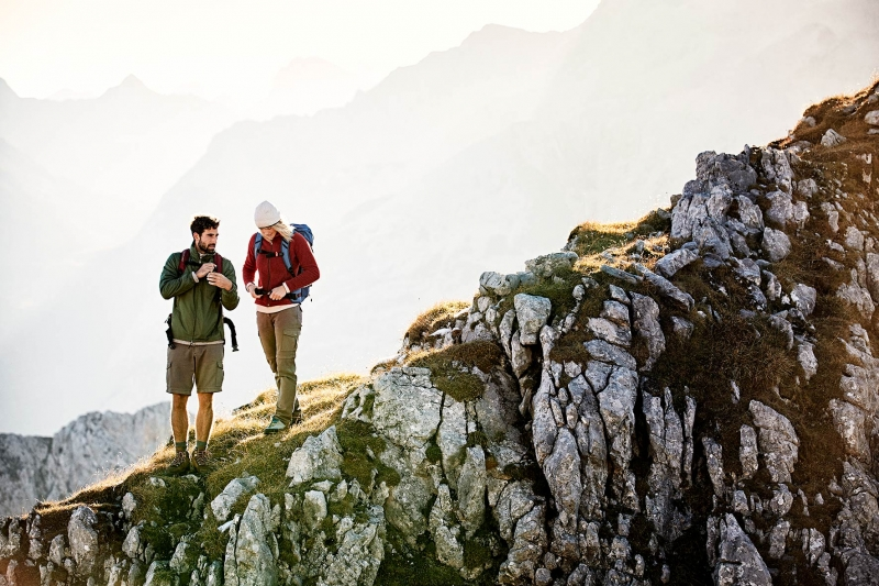 Couple trekking ontop of the Karwendel Mountain range, tightening their backpacks after a short break.