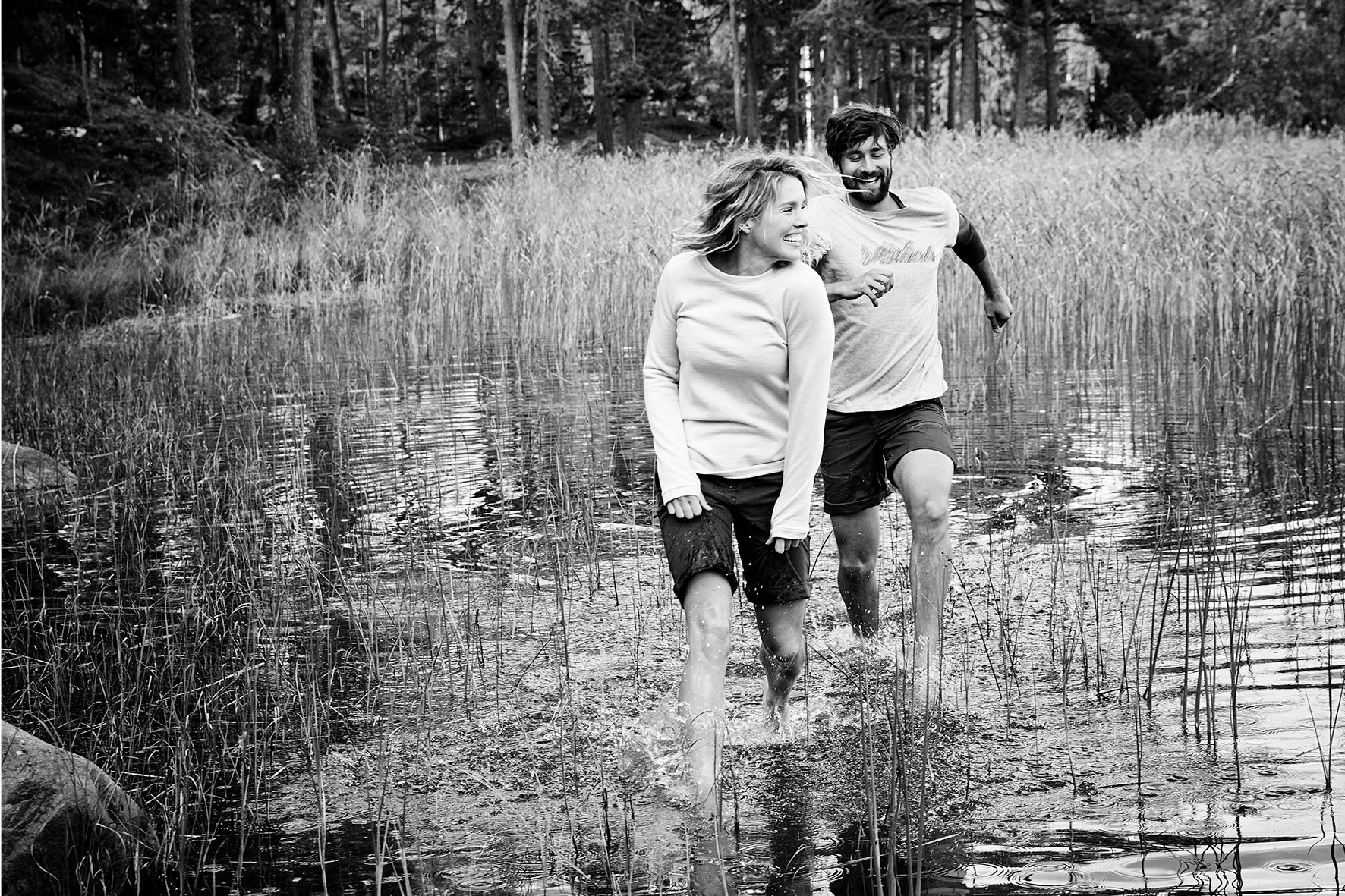 Black and white photo of a couple wearing fair fashion clothes while jumping barefoot through a lake near Stockholm, Sweden.